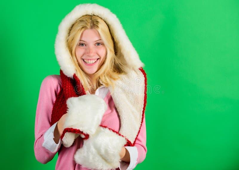 Vrouwen het emotionele gezicht stellen in warme bontkap Meisjes vrolijk blonde die de kap van het slijtagebont op groene achtergr stock afbeelding