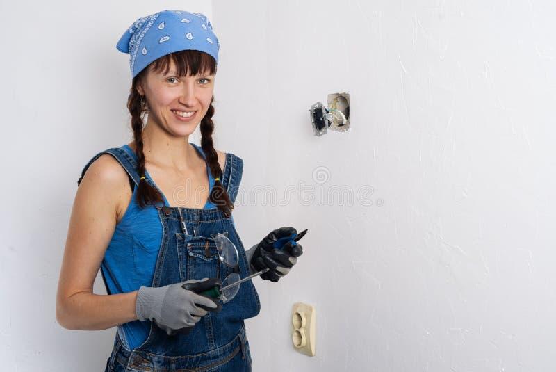 Vrouwen in het mannelijke beroep: Een glimlachend meisje herstelt een elektroschakelaar met een schroevedraaier en buigtang stock afbeelding