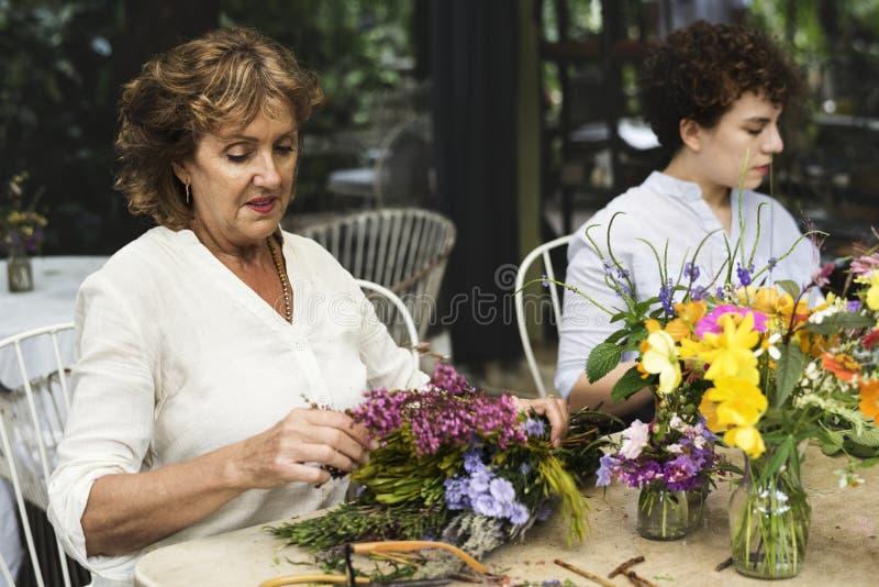 Vrouwen het schikken bloeit samen openlucht stock fotografie