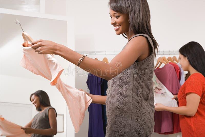 Vrouwen in klerenwinkel stock afbeeldingen