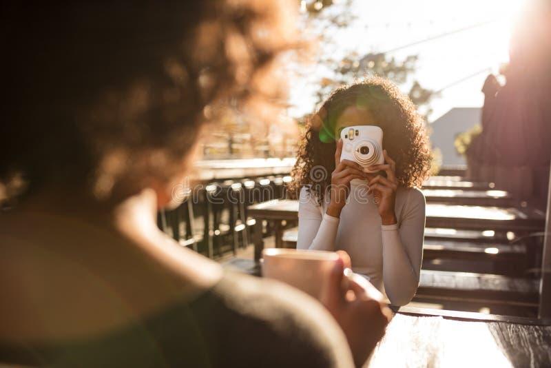 Vrouwen klikkende foto bij een koffiewinkel stock foto