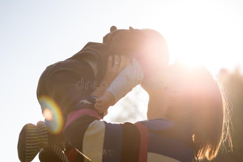 Vrouwen Kussende Baby Backlit door Helder Zonlicht stock afbeelding