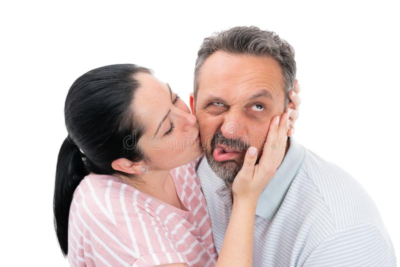 Vrouwen kussende man met weerzinwekkende uitdrukking stock afbeelding