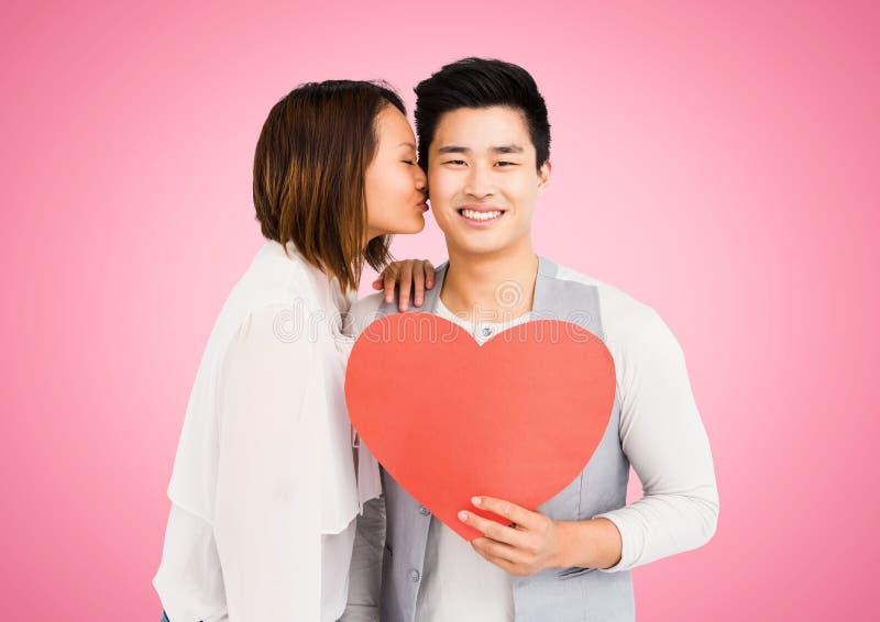 Vrouwen kussende man terwijl het houden van hart royalty-vrije stock afbeelding