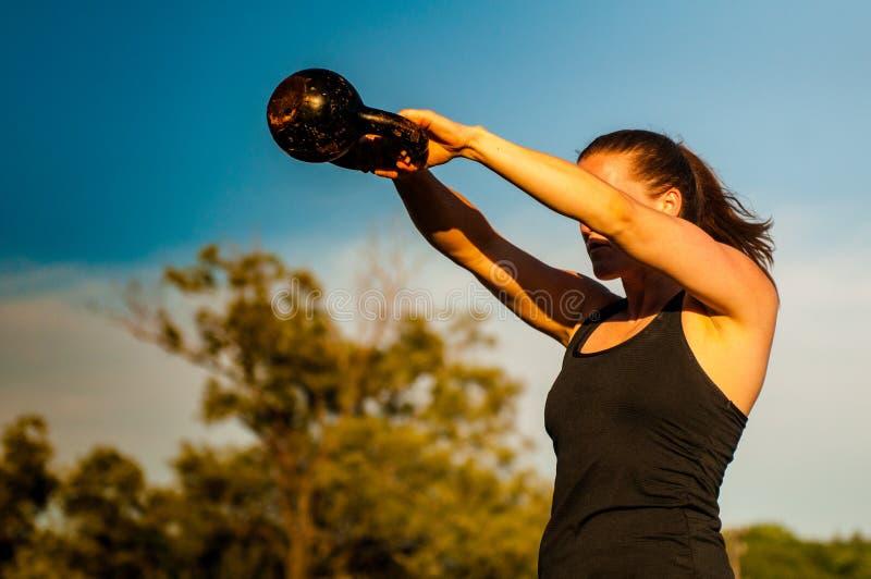 Vrouwen medio schommeling met kettlebell stock afbeeldingen
