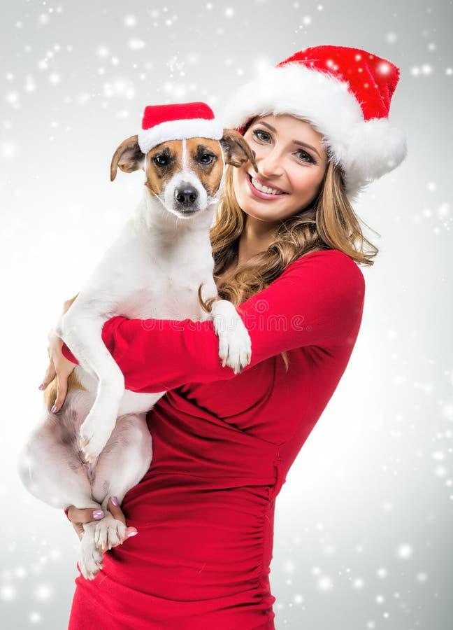Vrouwen met hond in Kerstmis Santa Hat stock afbeeldingen
