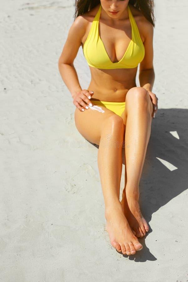 Vrouwen mooie benen op het strand Tan Woman Applying Sunscreen op Benen Close-up De zorg van de huid Schoonheidsmiddelen stock afbeeldingen