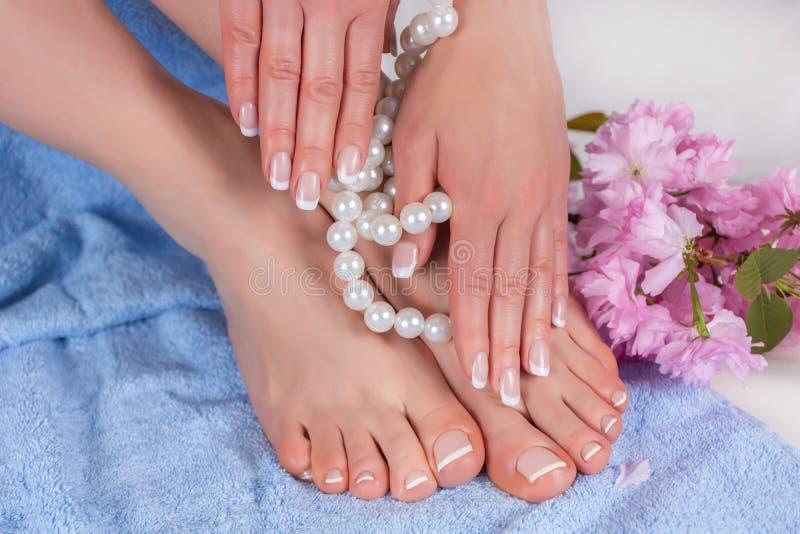 Vrouwen naakte voeten en handen met Franse manicure en pedicure in kuuroordsalon op blauwe blauwe handdoek met decoratieve bloem  stock fotografie