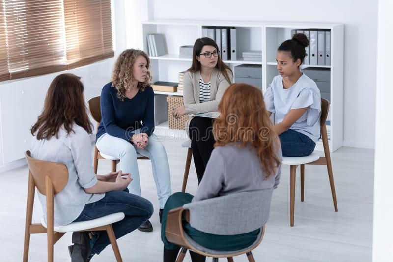 Vrouwen ondersteunend elkaar tijdens de vergadering van de psychotherapiegroep stock afbeeldingen