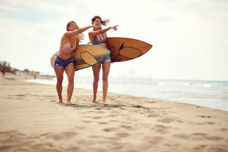 Vrouwen op strand die pret in de zomer hebben die surfen blijven stock afbeeldingen