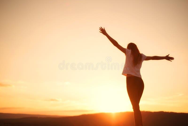 Vrouwen open wapens onder de zonsondergang Concept het gezonde leven royalty-vrije stock afbeeldingen