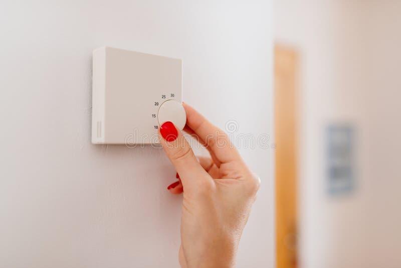Vrouwen regelende temperatuur op huis het verwarmen thermostaat stock foto's