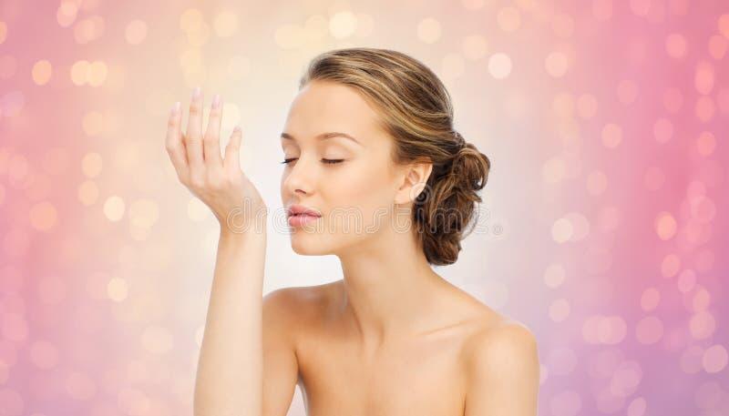 Vrouwen ruikend parfum van pols van haar hand royalty-vrije stock foto