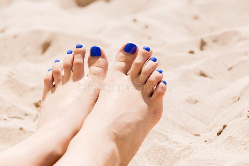 Vrouwen` s benen op het zand door het overzees royalty-vrije stock afbeelding