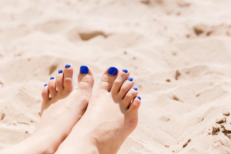 Vrouwen` s benen op het zand door het overzees stock afbeelding