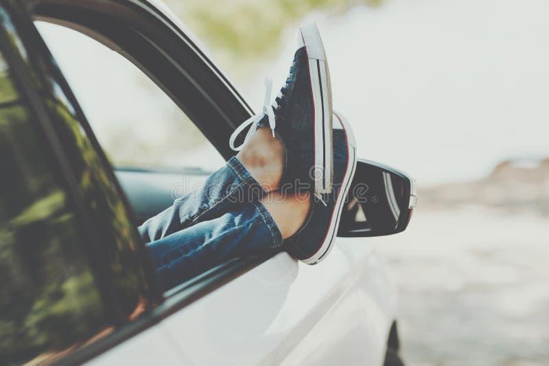 Vrouwen` s benen in tennisschoenen in de vensterauto Meisje in jeans in de auto met haar gekruiste benen stock foto's