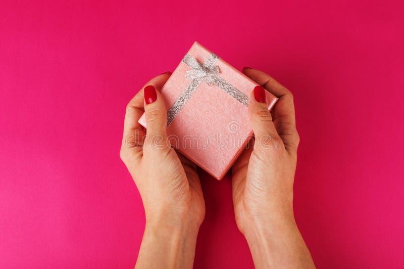 Vrouwen` s hand die een huidige doos op de roze achtergrond houden St de Dag van de valentijnskaart ` s royalty-vrije stock foto