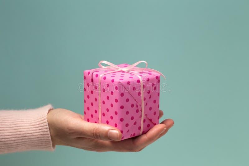 Vrouwen` s hand die roze giftdoos in stippen geven stock afbeeldingen