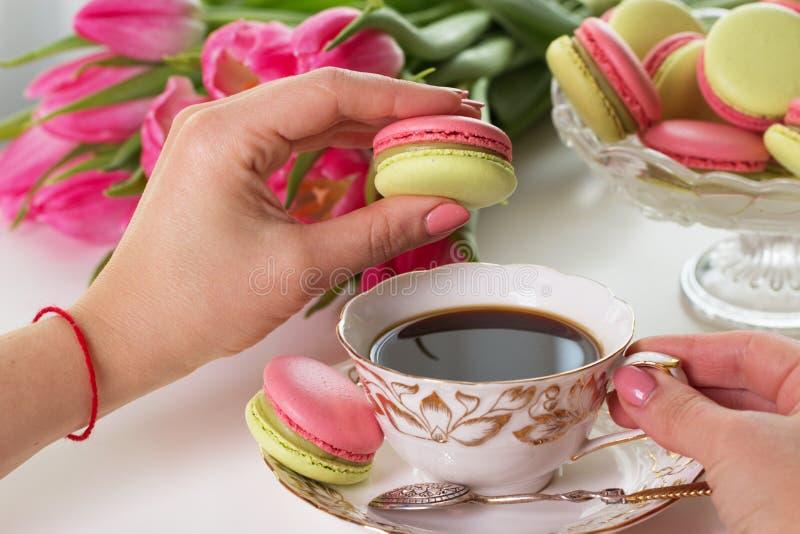 Vrouwen` s hand die roze makaron of macaron dessert houden royalty-vrije stock afbeeldingen