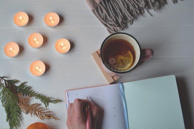 Vrouwen` s hand die in zuivelfabriek schrijven Decoratie op het witte houten bureau Atmosferische plaats voor het werk, kunst en  stock foto