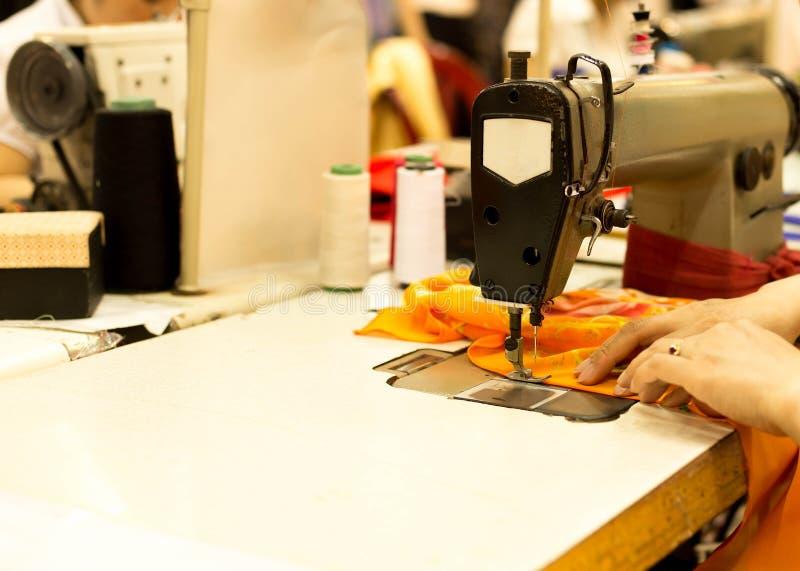 Vrouwen` s hand genaaide stof op oude naaimachine stock afbeelding