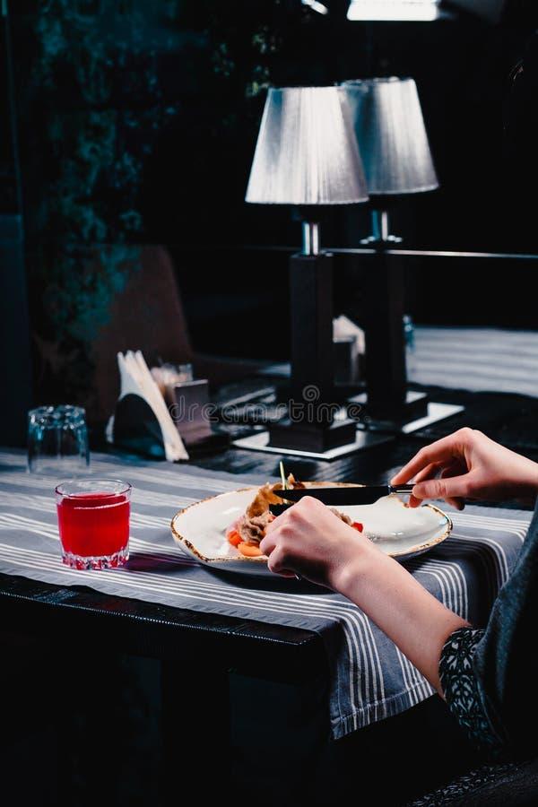 Vrouwen` s handen die en heerlijke salade met mes en vork snijden eten bij restaurant Naast een wit is de plaat een glas royalty-vrije stock foto's
