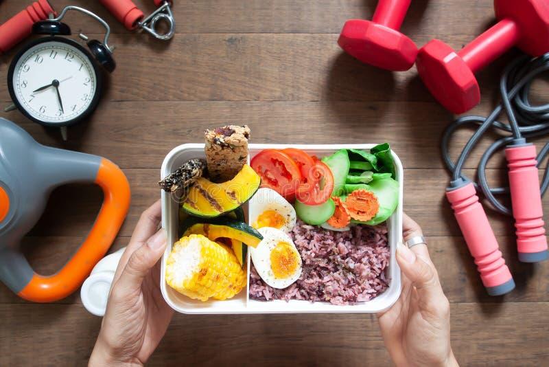 Vrouwen` s handen die lunchdoos met rijstbes houden, gekookte eieren, sw stock foto