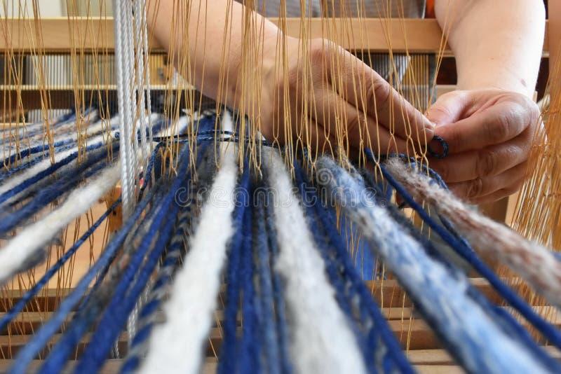 Vrouwen` s handen die op een weefgetouw weven royalty-vrije stock foto
