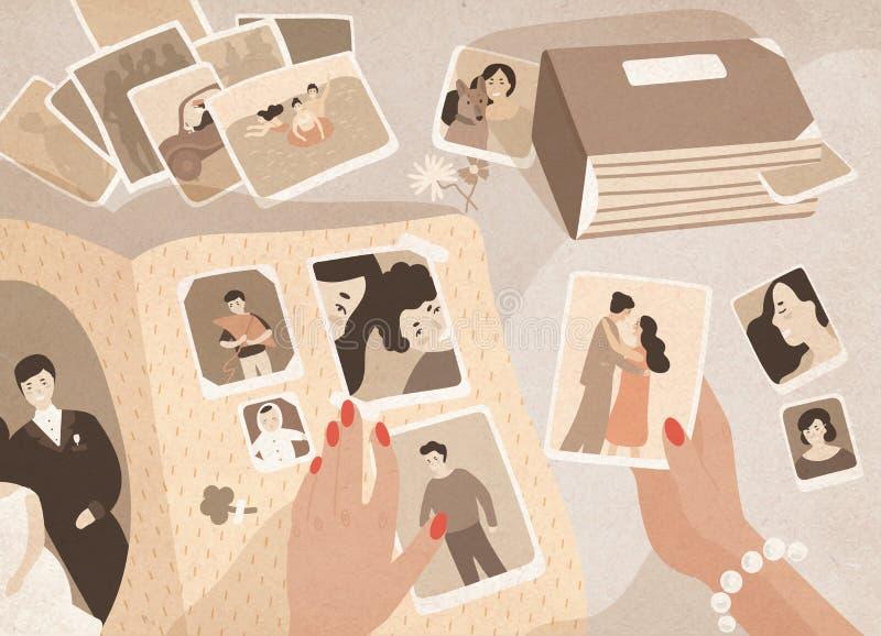 Vrouwen` s handen die oude foto's houden, hen regelen en aan pagina's van fotografisch album of fotoboek vastmaken royalty-vrije illustratie