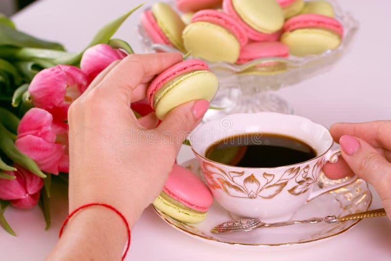 Vrouwen` s handen die roze makaron of macaron dessert houden makaron stock afbeeldingen