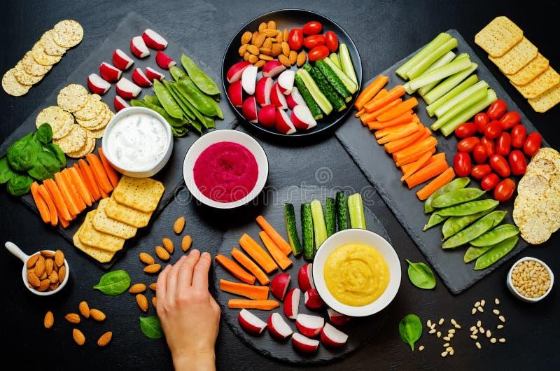 Vrouwen` s handen en variatie van gezonde veganistsnacks Groenten, crackers, onderdompeling en hummus stock foto