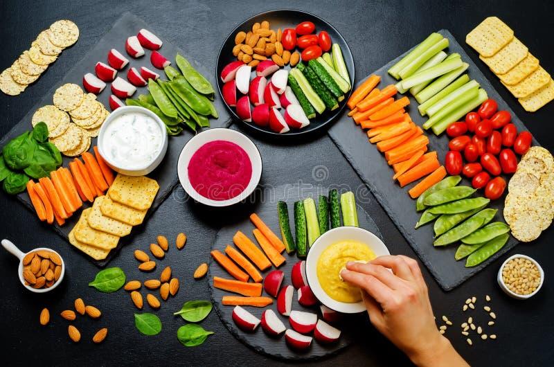Vrouwen` s handen en variatie van gezonde veganistsnacks Groenten, crackers, onderdompeling en hummus royalty-vrije stock afbeelding