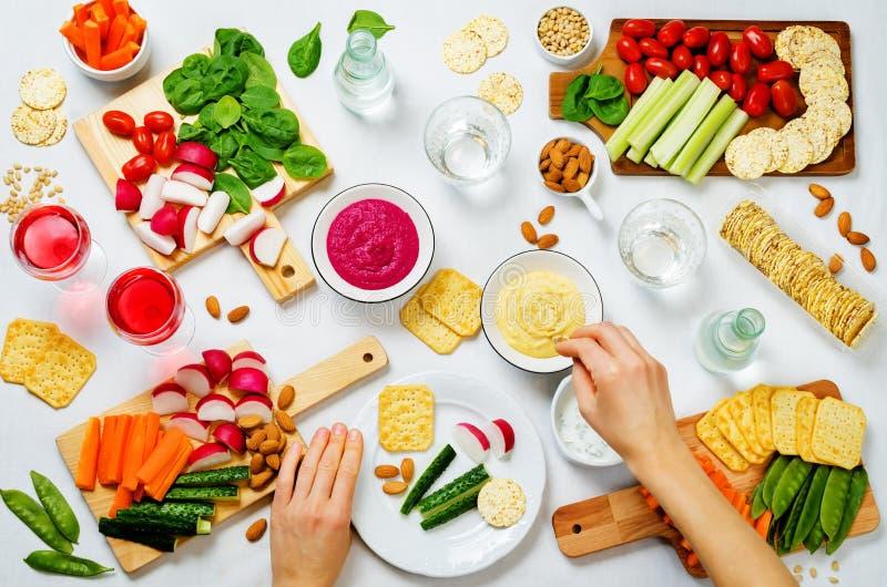 Vrouwen` s handen en variatie van gezonde veganistsnacks Groenten, crackers, onderdompeling en hummus royalty-vrije stock fotografie