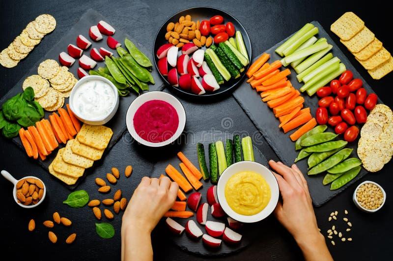 Vrouwen` s handen en variatie van gezonde veganistsnacks Groenten, crackers, onderdompeling en hummus stock fotografie