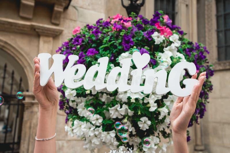Vrouwen` s handen met het woord van huwelijk op de achtergrond van bloemen en zeepbels royalty-vrije stock afbeeldingen