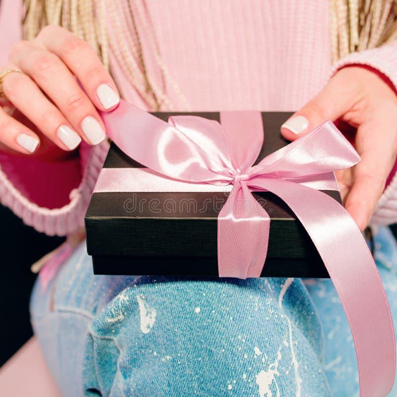 Vrouwen` s handen met roze manicure die zwarte huidige doos houden stock foto