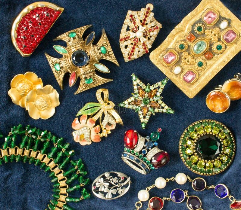 Vrouwen` s Juwelen Uitstekende luxueuze juwelenachtergrond Mooie bergkristallenbroches en oorringen op blauwe fluweelachtergrond  royalty-vrije stock fotografie