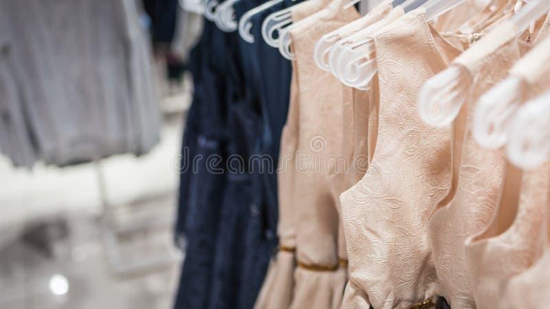 Vrouwen` s kleding op hangers in een kledingsopslag stock afbeeldingen