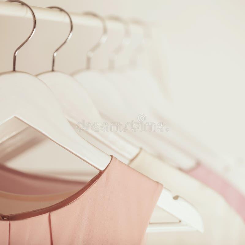 Vrouwen` s kleding in roze tonen op een witte hanger stock fotografie