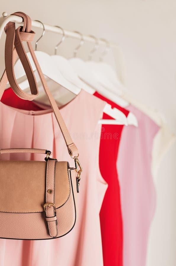 Vrouwen` s kleding in roze tonen op een witte hanger stock afbeeldingen