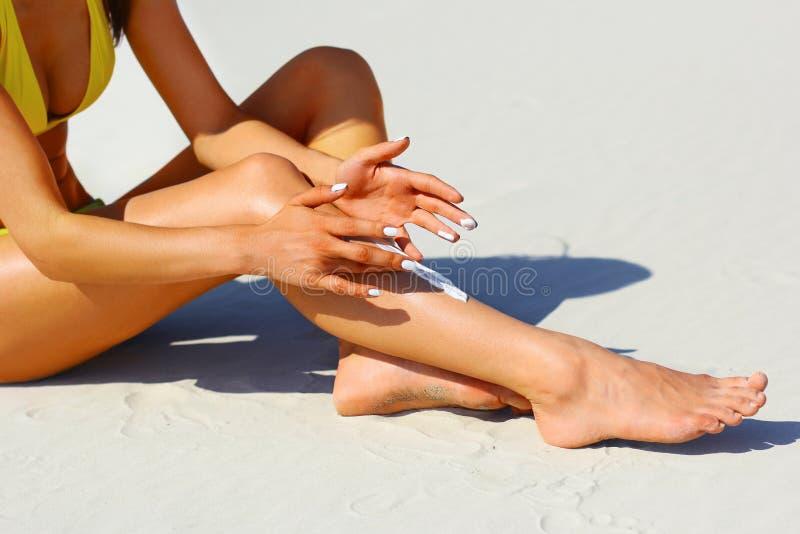 Vrouwen` s mooie benen op het strand Tan Woman Applying Sunscreen op Benen Close-up royalty-vrije stock fotografie