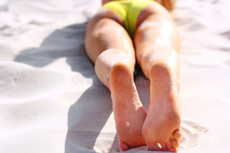 Vrouwen` s mooie benen op het strand Tan Woman Applying Sunscreen op Benen Close-up royalty-vrije stock afbeelding