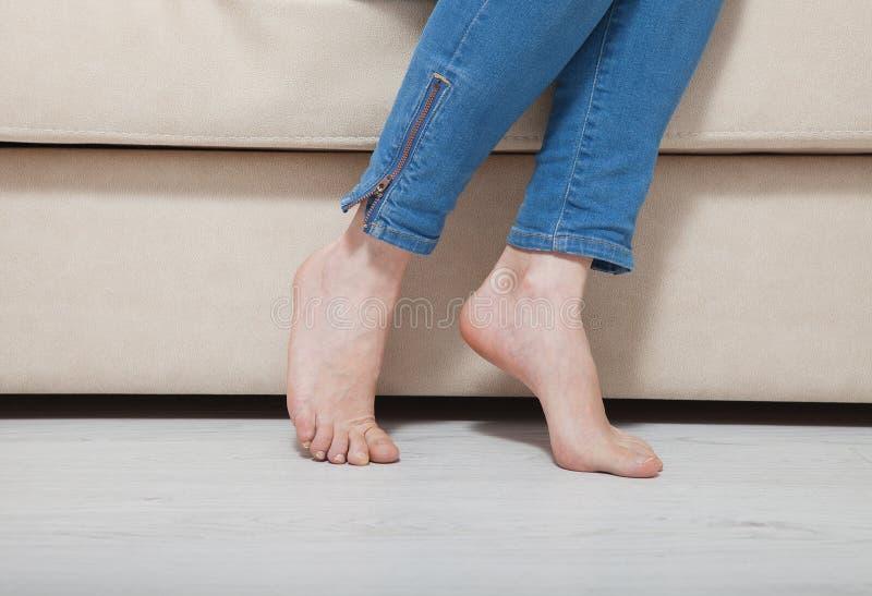 Vrouwen` s naakte voeten bij het theheating van vloer Benen in jeans die op laag zitten Macro Exemplaarruimte en spot omhoog royalty-vrije stock foto