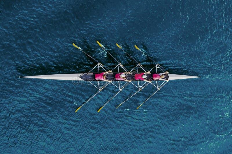 Vrouwen` s roeiend team op blauw water stock fotografie