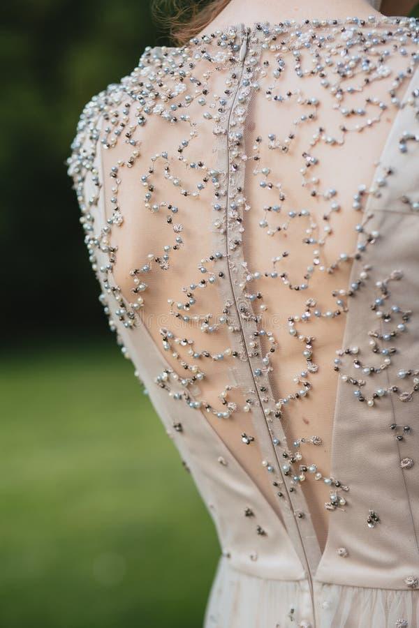 Vrouwen ` s terug in een mooie kleding met een besnoeiing en een borduurwerk van parels stock fotografie