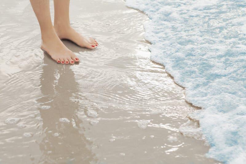 Vrouwen` s voeten die zich in branding bij het strand bevinden royalty-vrije stock foto