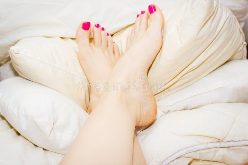 Vrouwen` s voeten, omhoog op de stapel van zachte hoofdkussens stock foto's