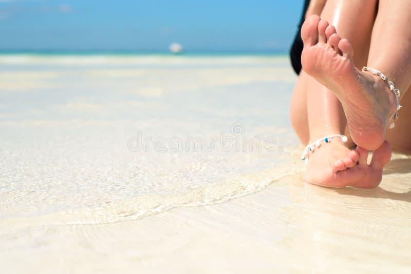 Vrouwen` s voeten, op het strand, concept, toerisme, pedicure, het verzorgen royalty-vrije stock afbeelding
