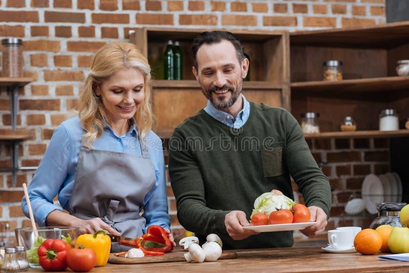 vrouwen scherpe groenten en echtgenoot die plaat zetten royalty-vrije stock afbeeldingen