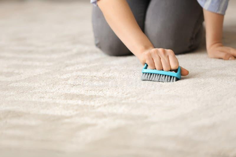 Vrouwen schoonmakend tapijt met borstel thuis royalty-vrije stock afbeelding